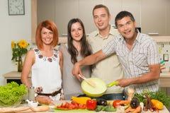 Amis heureux faisant cuire le dîner Images libres de droits