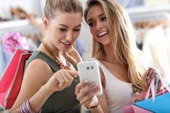Amis heureux faisant des emplettes dans le magasin avec le smartphone Photo libre de droits
