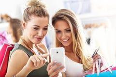 Amis heureux faisant des emplettes dans le magasin avec le smartphone Images libres de droits