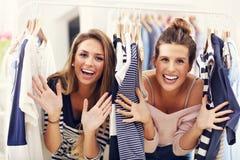 Amis heureux faisant des emplettes pour des vêtements Photos libres de droits