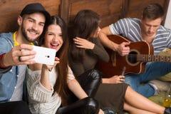 Amis heureux faisant des selfies et jouant la guitare Photos stock