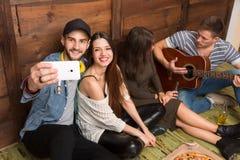 Amis heureux faisant des selfies et jouant la guitare Images stock