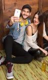 Amis heureux faisant des selfies tout en se reposant sur le plancher Photos libres de droits