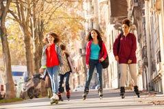 Amis heureux faisant du roller sur le trottoir en automne Image stock