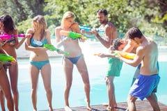 Amis heureux faisant l'échange de coups de feu de l'eau Photographie stock