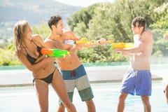 Amis heureux faisant l'échange de coups de feu de l'eau Photographie stock libre de droits