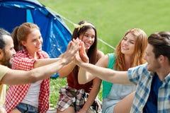 Amis heureux faisant la haute cinq au camping Photographie stock libre de droits