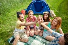 Amis heureux faisant la haute cinq au camping Photographie stock
