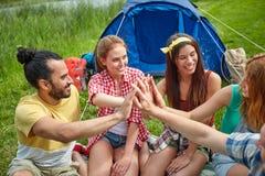 Amis heureux faisant la haute cinq au camping Photos libres de droits