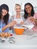 Amis heureux faisant la pâtisserie regardant ensemble l'appareil-photo Image libre de droits