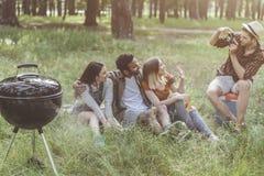 Amis heureux faisant la photo près du brasero Images stock