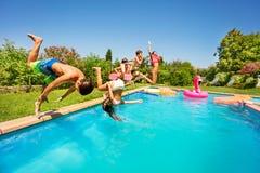 Amis heureux faisant la secousse avant dans la piscine photographie stock