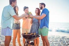 Amis heureux faisant le barbecue et buvant de la bière Image stock