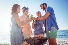 Amis heureux faisant le barbecue et buvant de la bière Photographie stock libre de droits