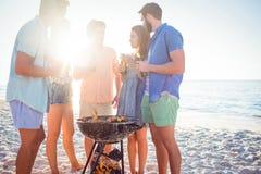 Amis heureux faisant le barbecue et buvant de la bière Photos stock