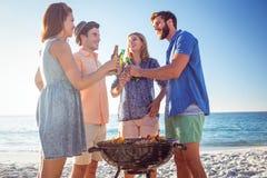 Amis heureux faisant le barbecue et buvant de la bière Photos libres de droits