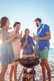 Amis heureux faisant le barbecue et buvant de la bière Photographie stock