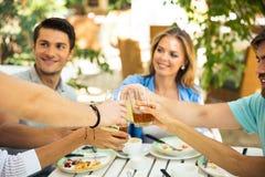 Amis heureux faisant le pain grillé autour de la table Photos stock