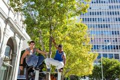 Amis heureux faisant le parkour dans la ville Images libres de droits