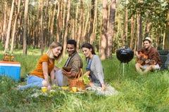 Amis heureux faisant le pique-nique en nature Image stock