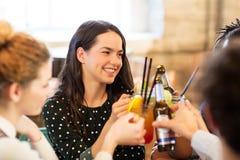 Amis heureux faisant tinter des boissons à la barre Photo stock