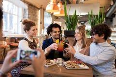 Amis heureux faisant tinter des boissons à la barre ou au café Photographie stock