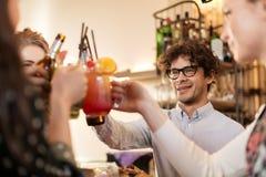Amis heureux faisant tinter des boissons à la barre ou au café Photos libres de droits
