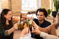 Amis heureux faisant tinter des boissons à la barre ou au café Photo stock