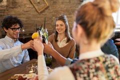 Amis heureux faisant tinter des boissons à la barre ou au café Image libre de droits