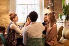 Amis heureux faisant tinter des boissons à la barre ou au café Photo libre de droits