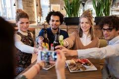 Amis heureux faisant tinter des boissons à la barre ou au café Image stock