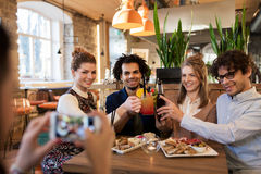 Amis heureux faisant tinter des boissons à la barre ou au café Images libres de droits
