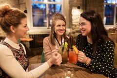 Amis heureux faisant tinter des boissons au restaurant Photographie stock libre de droits
