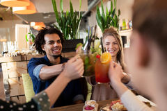 Amis heureux faisant tinter des boissons au restaurant Photographie stock