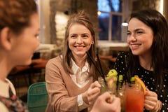 Amis heureux faisant tinter des boissons au restaurant Photos libres de droits