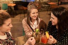 Amis heureux faisant tinter des boissons au restaurant Photos stock