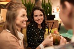 Amis heureux faisant tinter des boissons au restaurant Image libre de droits