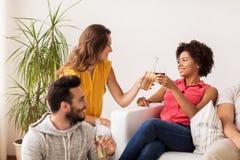 Amis heureux faisant tinter des bouteilles de bière à la maison Image libre de droits