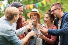 Amis heureux faisant tinter des verres au jardin d'été Images stock