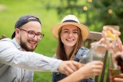 Amis heureux faisant tinter des verres au jardin d'été Photographie stock libre de droits