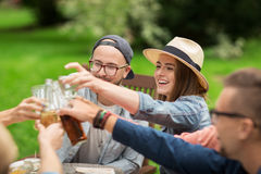 Amis heureux faisant tinter des verres au jardin d'été Photos stock