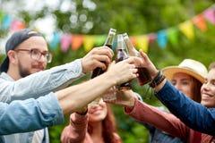 Amis heureux faisant tinter des verres au jardin d'été Image libre de droits