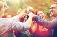 Amis heureux faisant tinter des verres au jardin d'été Photo stock