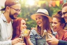 Amis heureux faisant tinter des verres au jardin d'été Photo libre de droits