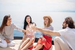 Amis heureux faisant tinter des verres de champagne et naviguant sur le yacht Image libre de droits