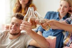 Amis heureux faisant tinter la partie de bouteilles à bière à la maison Photo stock