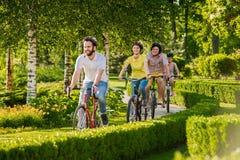 Amis heureux faisant un cycle en parc de ville Image libre de droits