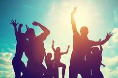 Amis heureux, famille sautant ensemble ayant l'amusement