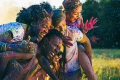 Amis heureux ferroutant ensemble au festival de holi Image stock