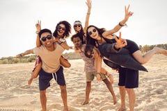 Amis heureux ferroutant leurs amies au coucher du soleil Photo stock